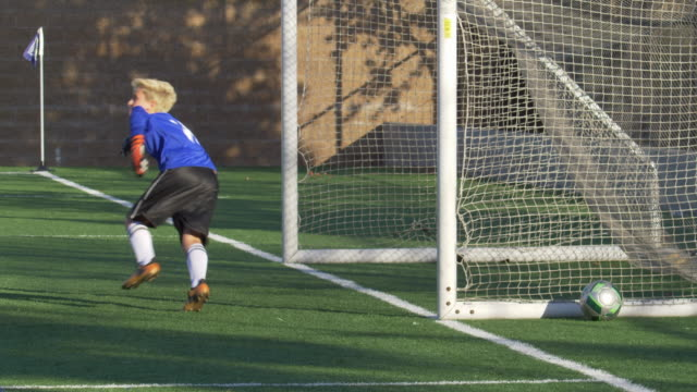 a boy scoring while playing youth soccer football goalie goalkeeper on a turf grass field. - slow motion - netting stock videos & royalty-free footage