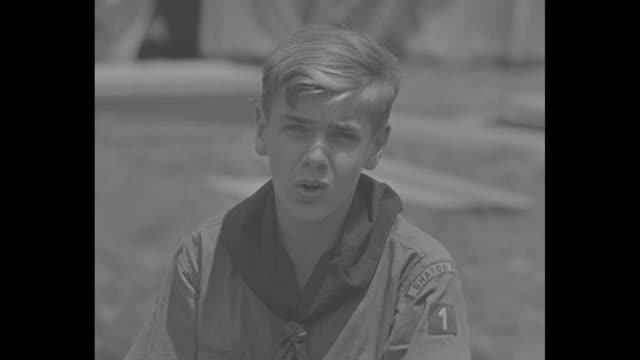 boy scout alfred hoffner from springfield pa walks past tents carrying bucket of water and sets it down next to men stacking wood boards / cu one man... - ladle stock videos & royalty-free footage
