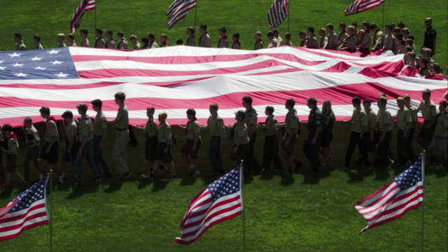 Boy Scouts carring American Flag across field.