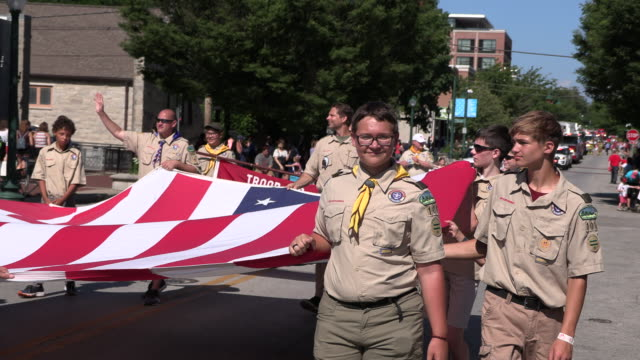 boy scouts carry a large united states flag during the 4th of july parade, thursday, july 4, 2019 in bloomington, ind. - boy scout stock videos & royalty-free footage