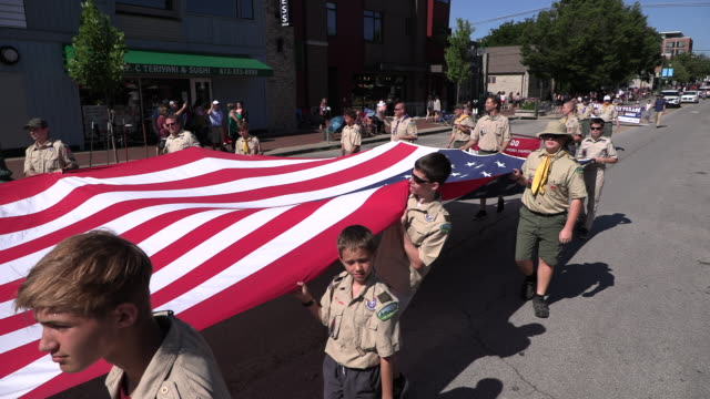 boy scouts carry a large united states flag during the 4th of july parade, thursday, july 4, 2019 in bloomington, ind. - scout association stock videos & royalty-free footage