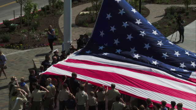 boy scouts holding american flag as it is being strung up a pole. - boy scout stock videos & royalty-free footage