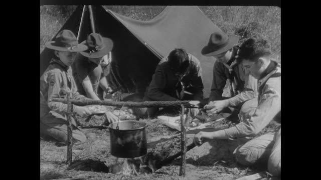 boy scouts prepare food outside tent - guerra del pacifico video stock e b–roll