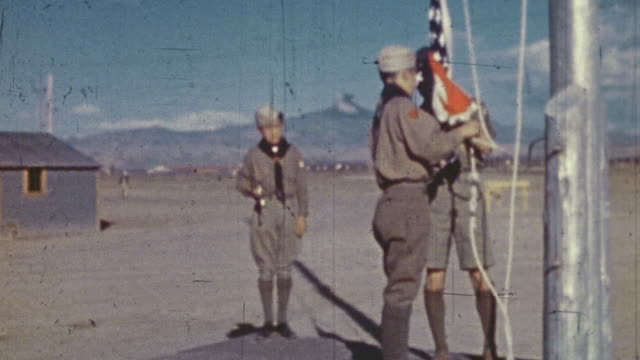 boy scouts raising an american flag at a world war ii war relocation center for interned citizens / united states - boy scout stock videos & royalty-free footage