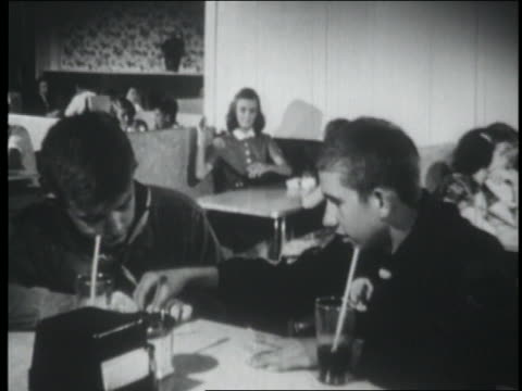 b/w 1953 2 boy scouts sit at counter in soda fountain / 2 girls in booth in background throw things at them - scout association stock videos & royalty-free footage