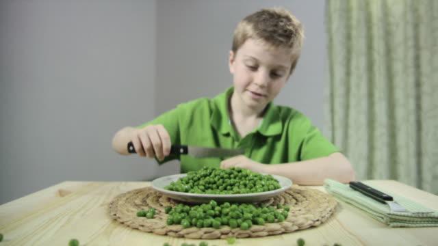 vídeos y material grabado en eventos de stock de boy scraping peas off plate with knife - camisa de polo