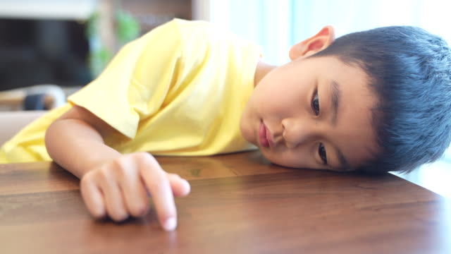 boy scratching the table while messing around - 負の感情点の映像素材/bロール