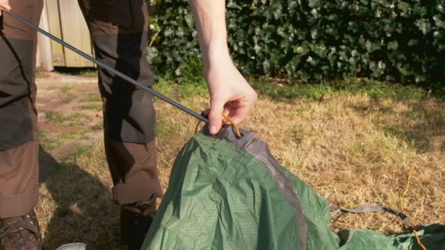 vídeos y material grabado en eventos de stock de boy setting up tent - un solo adolescente