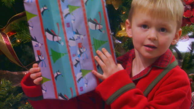 Boy shaking presents, slow motion