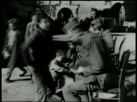 boy shining soldier's shoes on sidewalk makeshift shoe stand film clip vittorio desica's 1946 film 'sciuscia' w/ shoeshine boy receiving present from... - 1946 stock-videos und b-roll-filmmaterial