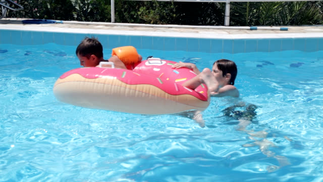boy shooting video in swimming pool - arm band stock videos & royalty-free footage