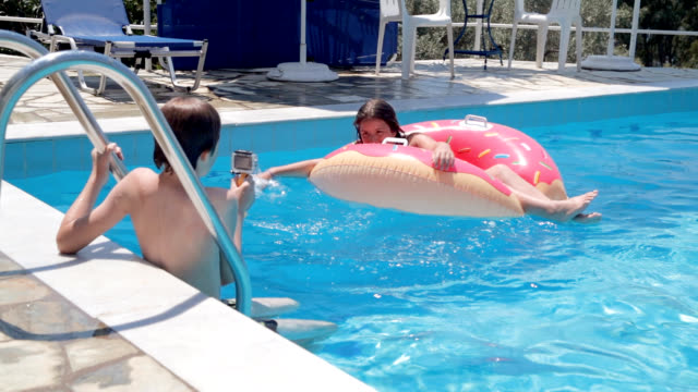 Junge Videoaufnahmen seiner Schwester im Schwimmbad