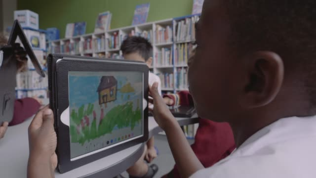 boy showing drawing to friends in school - library stock videos & royalty-free footage