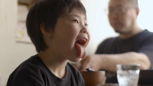 a boy showing funny faces with tongue out - 人間の舌点の映像素材/bロール