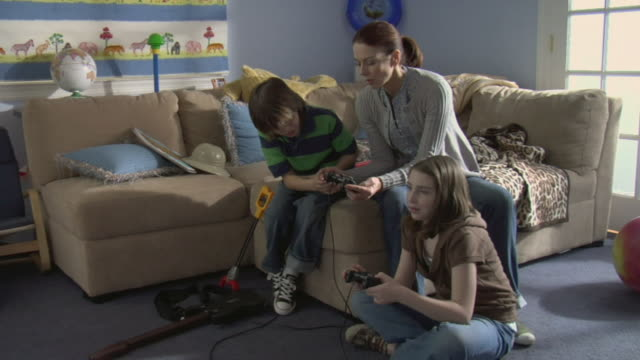 ms boy showing mother how to play video game as girl sits on floor playing game/ white plains, new york - moving down to seated position stock videos & royalty-free footage
