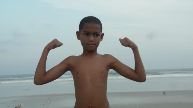 vídeos y material grabado en eventos de stock de ms boy (8-9) showing of his muscles on beach / jacksonville, florida, usa - flexionar los músculos