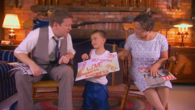 boy showing parents a poster in living room, 1950's - retro poster stock videos & royalty-free footage