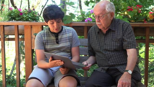 boy shows a computer program to his grandfather - ワーキングシニア点の映像素材/bロール