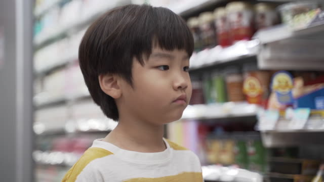 boy sighing at food price with eggs in his hands, seoul, south korea - display cabinet stock videos & royalty-free footage