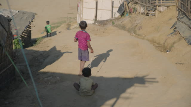 A boy sits in a plastic tub as another drags him with a string in Kutupalong refugee camp in Bangladesh Children make up over 50% of those in the...
