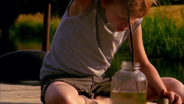 A boy sits on a dock stirring moss in a jar with a stick.
