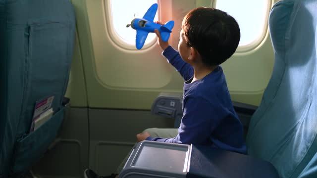 un ragazzo si siede su una finestra vicino a un aereo commerciale. nella sua mano stava giocando un aereo giocattolo con un sogno che vorrebbe viaggiare in aereo o diventare un pilota. - interno di veicolo video stock e b–roll