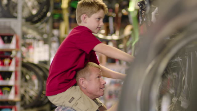 boy sits on father's shoulders, points at bicycles and looks at price tags in bike shop - hoch position stock-videos und b-roll-filmmaterial