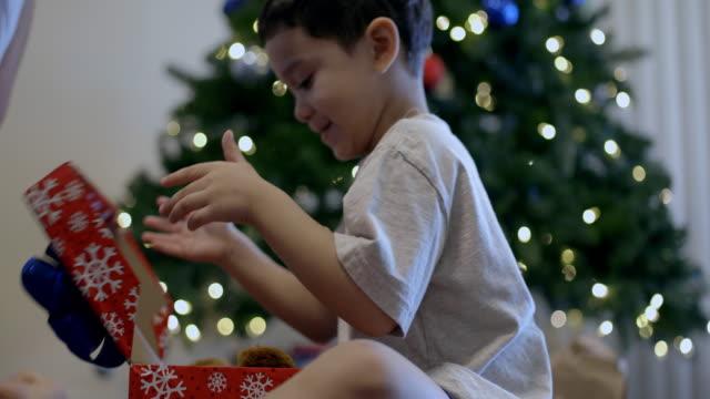 vídeos y material grabado en eventos de stock de boy sits on floor carefully opening christmas present, he takes out a teddy bear and hugs it - osito de peluche