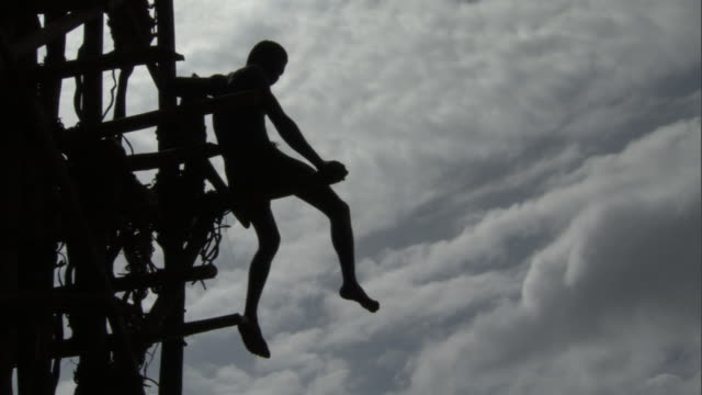 Boy sits on wooden tower during land diving ritual, Pentecost, Vanuatu
