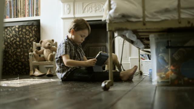 boy sitting and playing with digital tablet in room. - auf dem boden sitzen stock-videos und b-roll-filmmaterial