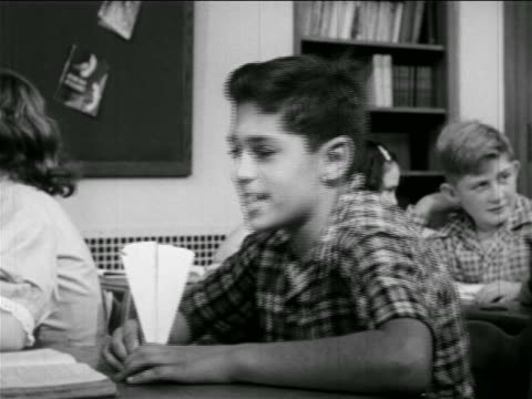 B/W 1951 boy sitting at desk in classroom standing up + starting to throw paper airplane