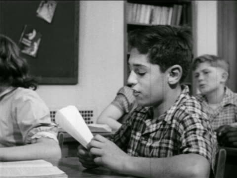 B/W 1951 boy sitting at desk talking + making paper airplane in classroom / educational