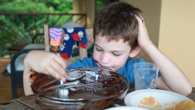 boy sitting at table eating from a bowl of chocolate. - kelly mason videos 個影片檔及 b 捲影像