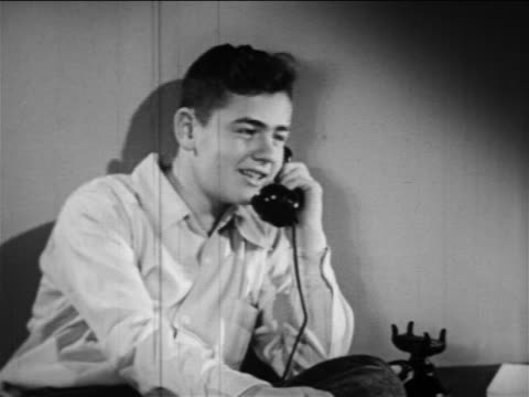 b/w 1949 boy sitting at table talking on telephone / educational - one teenage boy only stock videos & royalty-free footage