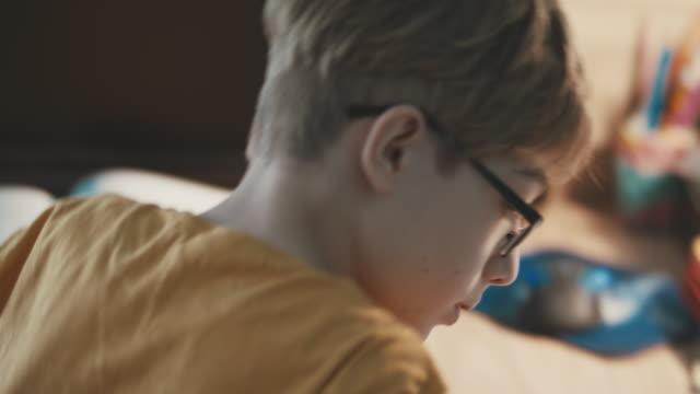 vídeos de stock, filmes e b-roll de rapaz sentado na mesa fazendo sua lição de casa - óculos