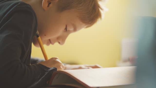 vidéos et rushes de garçon assis à la table, faire ses devoirs - carnet