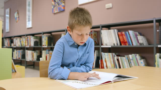 ds boy sitting at the table in library and reading - bookshelf stock videos & royalty-free footage