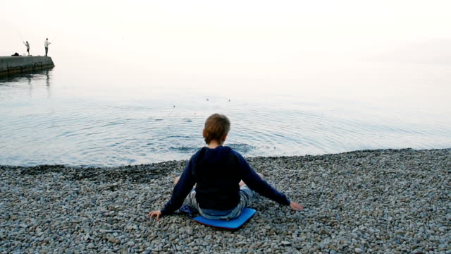 boy sitting at the water's edge on the beach, rear view