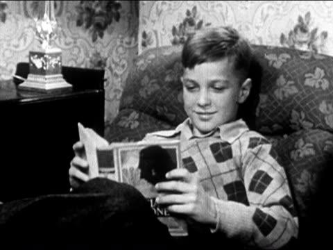 vídeos de stock e filmes b-roll de 1950 boy sitting down in armchair to read book / usa / audio - ler