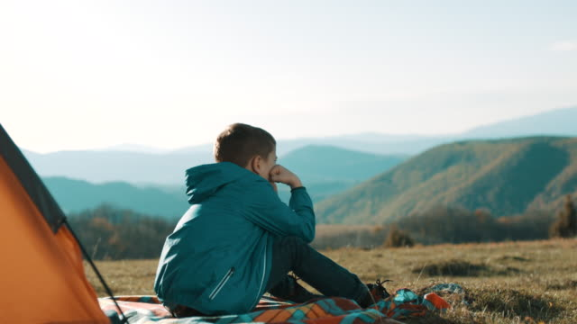 boy sitting in front of the tent on top of the mountain - boys stock videos & royalty-free footage