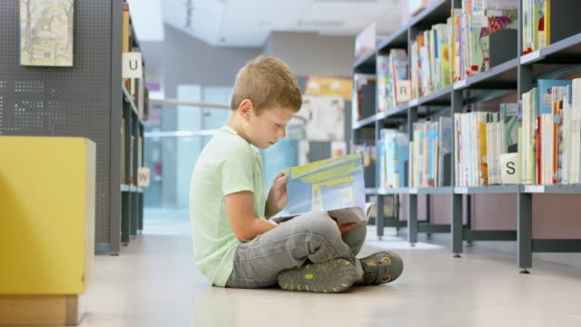 ds pojke sitter i biblioteket mittgång en bok - 6 7 år bildbanksvideor och videomaterial från bakom kulisserna