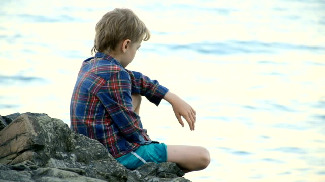 boy sitting on a large boulder on the beach