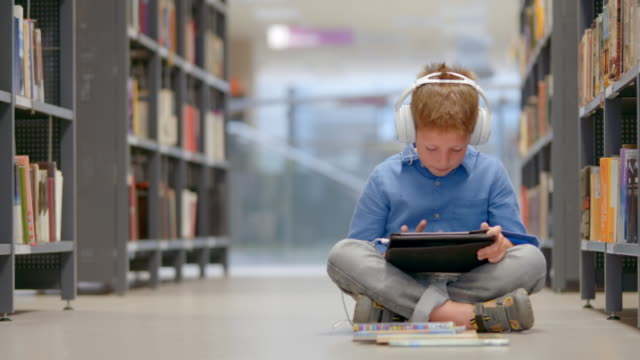 ds boy sitting on a library aisle and browsing on his tablet - headphones stock videos & royalty-free footage