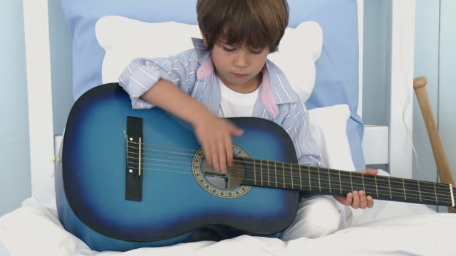 ws boy (4-5) sitting on bed and playing acoustic guitar / cape town, south africa - ギター点の映像素材/bロール