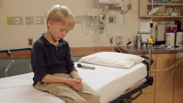 ms boy (8-9) sitting on bed in exam room / portland, maine, usa - 病棟点の映像素材/bロール