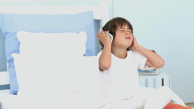 stockvideo's en b-roll-footage met ms boy (4-5) sitting on bed listening to music on headphones / cape town, south africa - tanden op elkaar klemmen