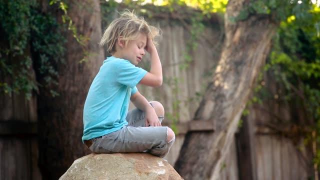 boy sitting on boulder - 8 9 år bildbanksvideor och videomaterial från bakom kulisserna