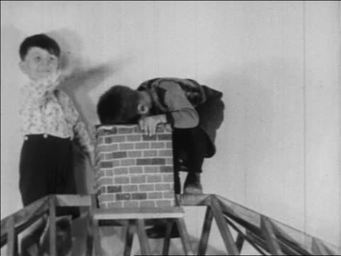 b/w 1934 boy sitting on chimney of playhouse in nursery school / wpa project / newsreel - playhouse stock videos and b-roll footage
