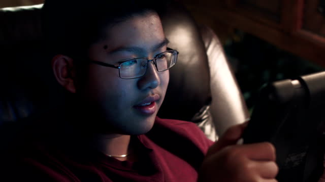 boy sitting on couch using a digital tablet at night - one teenage boy only stock videos & royalty-free footage