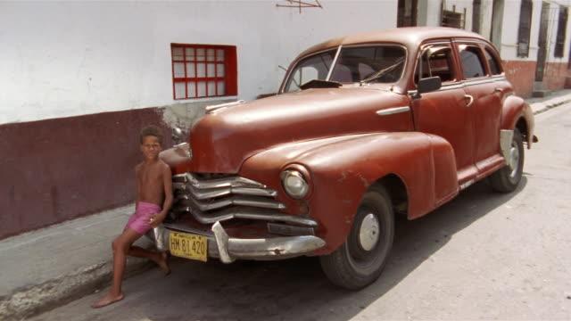 vídeos de stock e filmes b-roll de ms, boy (10-11) sitting on fender of red vintage car, havana, cuba  - para choques